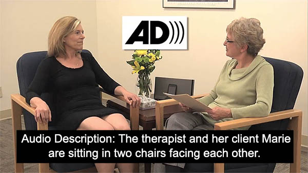 """Photo of a woman talking with another person. A caption reads """"Audio Description: The therapist and her client Marie are sitting in two chairs facing each other."""""""