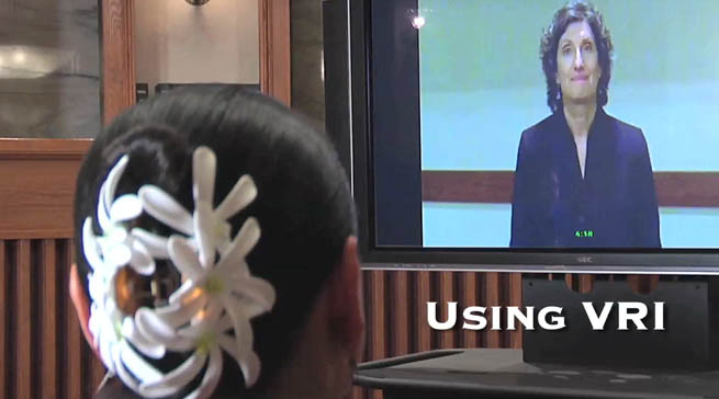 A deaf woman is in front of a TV monitor displaying an ASL Interpreter with the following text overlaid: Using VRI