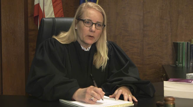 A judge sitting at her bench talking with a juvenile victim of sex trafficking