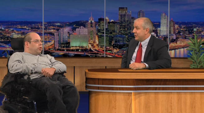 Photo of TV setting with a man in a wheel chair chatting with a talk show host