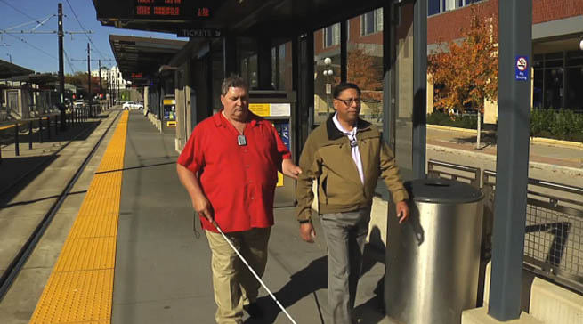 Photo of a deafblind man with a cane walking with his SSP at the light rail station