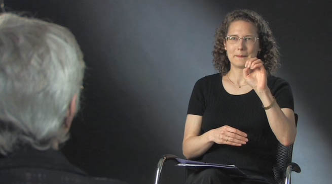 Photo of a deaf woman signing with another deaf woman in an interview setting
