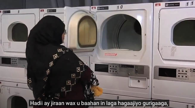 A Somali woman is loading laundery to a washing machine
